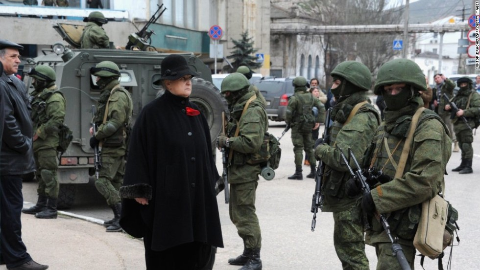 A woman waits in front of unidentified men in military fatigues who were blocking a base of the Ukrainian frontier guard unit in Balaklava, Ukraine, on Saturday, March 1.