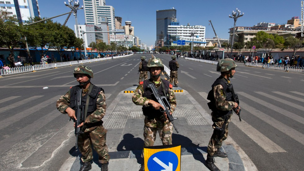 Armed paramilitary policemen guard a crossing in front of Kunming Railway Station in Kunming after a Saturday attack that left dozens dead.