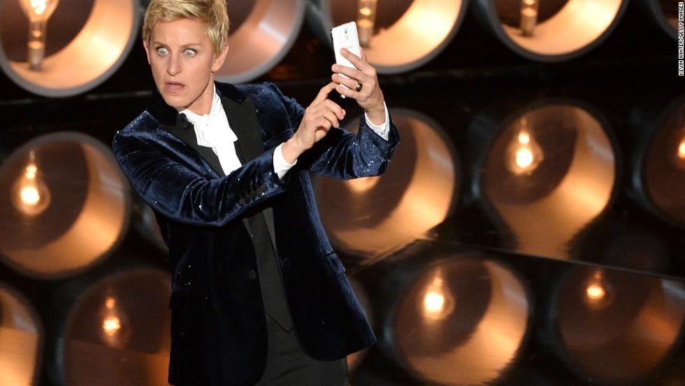 "DeGeneres <a href=""https://twitter.com/TheEllenShow/status/440302561044594688"" target=""_blank"">takes a selfie</a> on stage near the start of the show."