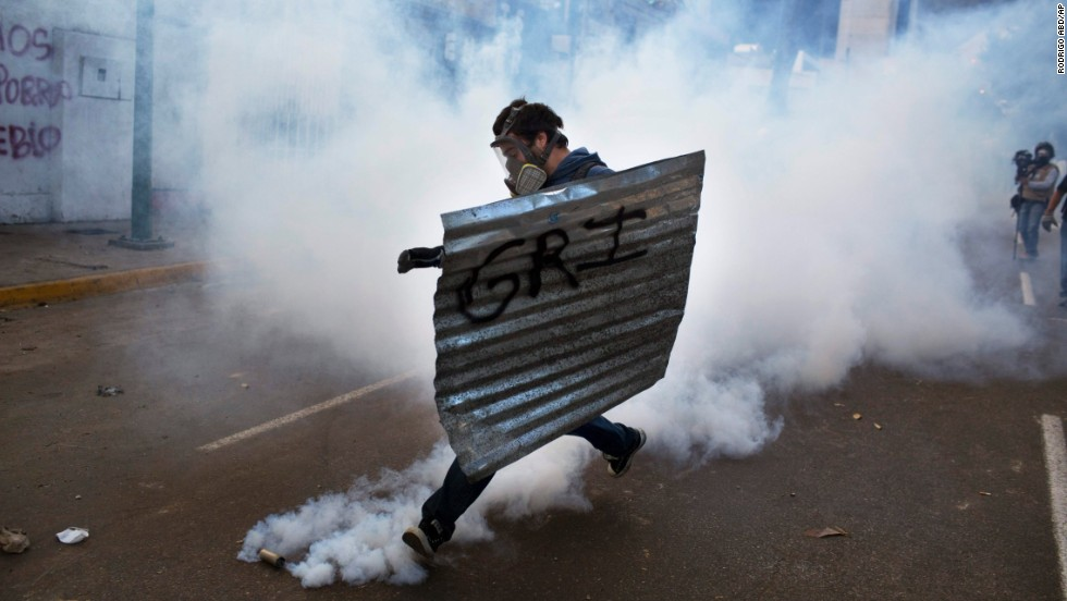 A masked protester with a makeshift shield kicks a tear gas canister launched by the National Guard during clashes in Caracas on Sunday, March 2.