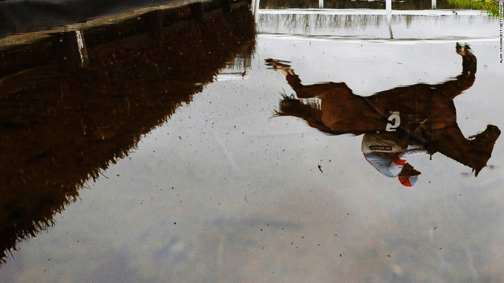 A reflection in the water shows Aidan Coleman riding Stone Light as they jump at the Newbury Racecourse in Newbury, England, on Friday, February 28.