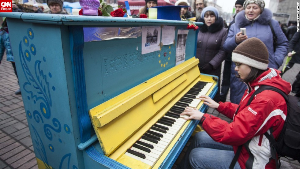 "A young girl plays <a href=""http://ireport.cnn.com/docs/DOC-1098749"">piano</a> in downtown Kiev 10 days after protests there."
