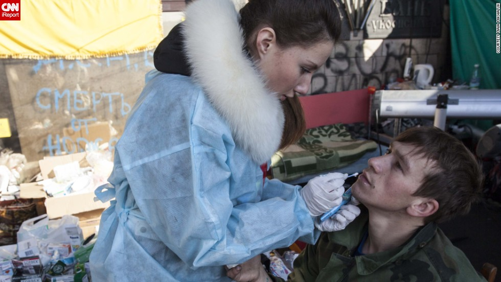 A woman tends to the wounds of a Ukrainian soldier.