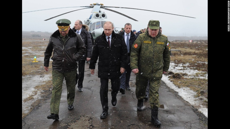 Putin, center, and Defense Minister Sergei Shoigu, left, arrive to watch a March 2014 military exercise at the Kirillovsky firing ground in Russia's Leningrad region.