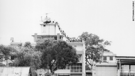 29 Apr 1975 --- A CIA employee (probably O.B. Harnage) helps Vietnamese evacuees onto an Air America helicopter from the top of 22 Gia Long Street, a half mile from the U.S. Embassy. --- Image by © Bettmann/CORBIS