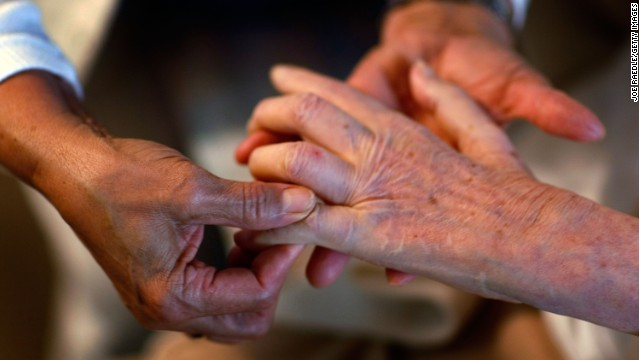 A home health aide massages the fingers of a woman in her care. Olympia Dukakis says home care workers are indispensable.