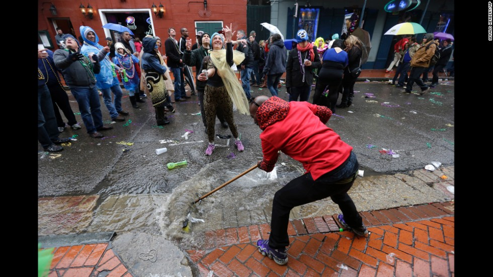 People in the streets yell for beads while a man sweeps rainwater in the French Quarter. The rain and unusually cold temperatures in New Orleans kept most of the normally massive crowds away.