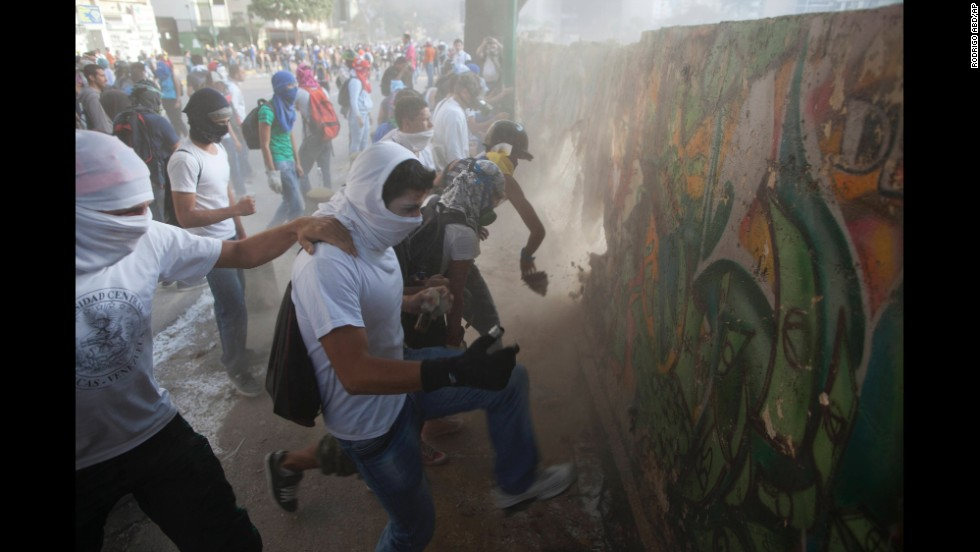 Protesters destroy a wall March 4 to get more rocks to throw at riot police in Caracas.