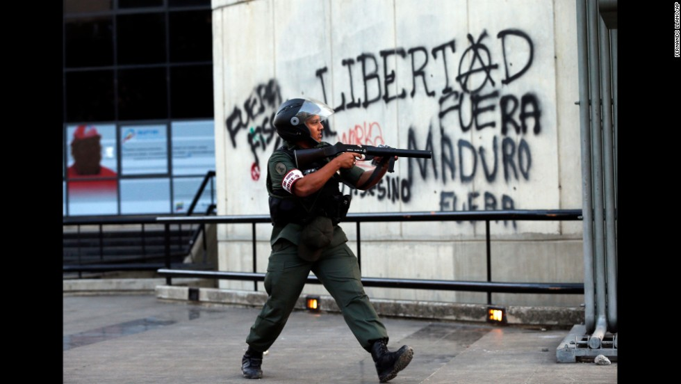 A National Guard officer points a tear gas launcher at demonstrators in Caracas on March 4.