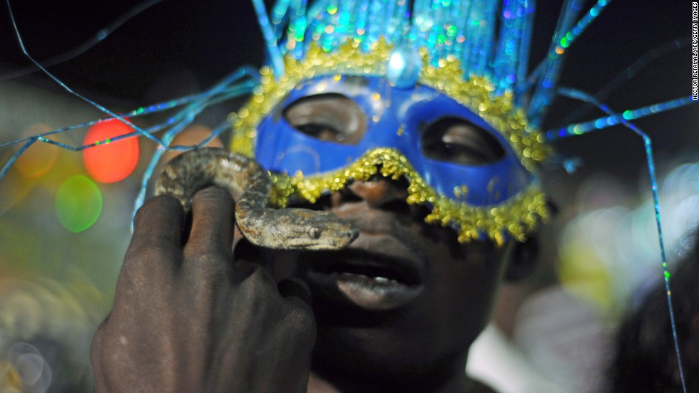 A masked man holds up his snake during the last day of the National Carnival Parade in Gonaives, Haiti, on March 4. Carnival is a circus-like celebration that traditionally occurs before Lent around the world.