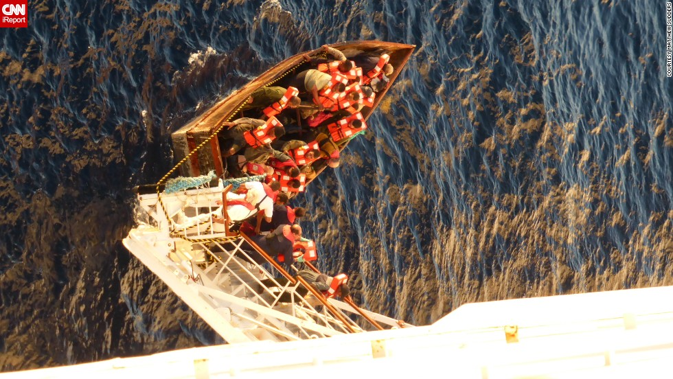 iReporter Matthew Sudder leaned over the railing of the Paradise to get this shot of the boat's passengers boarding the ship, wearing  life jackets provided by the ship's crew. They were given water, food, clothing, accommodations and medical care.