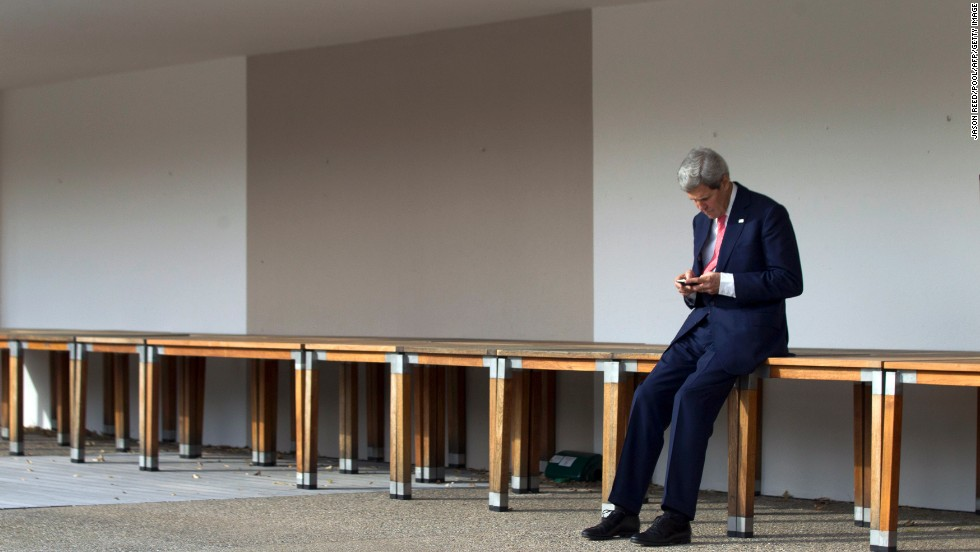 Kerry checks his cell phone in Geneva, Switzerland, prior to a November 2103 meeting with Iran's foreign minister and the European Union's high representative for foreign affairs.