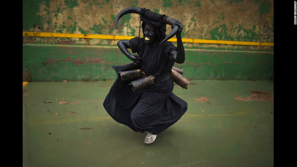 A woman, covered in oil and soot, carries bull horns on her head and cowbells on her belt to represent the devil during carnival celebrations in Luzon, Spain, on Saturday, March 1.