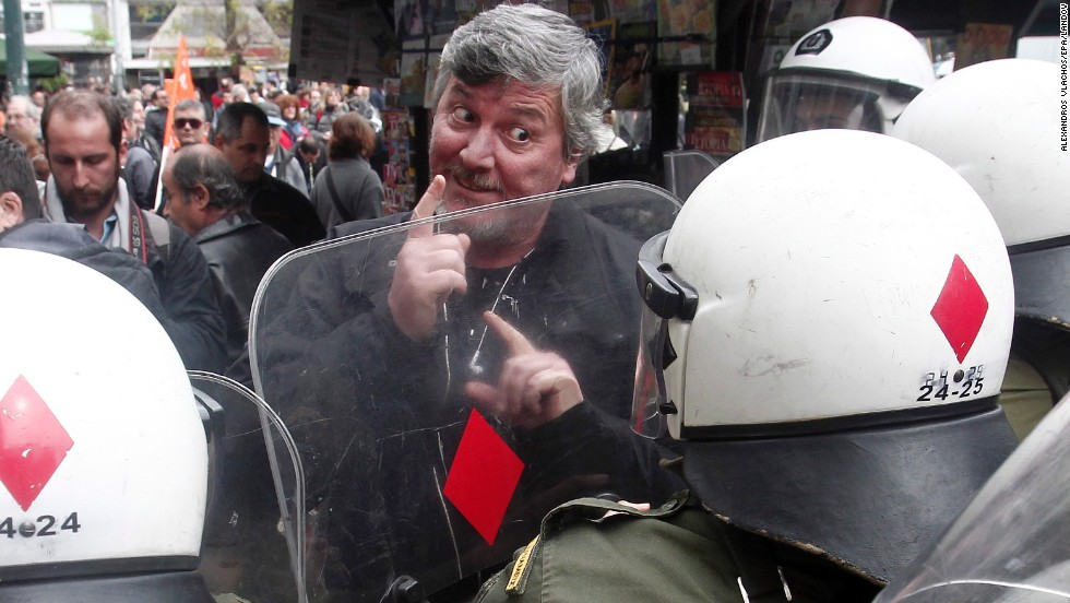 Municipal employees and school guards scuffle with riot police outside the Finance Ministry in Athens, Greece, on Friday, February 28.