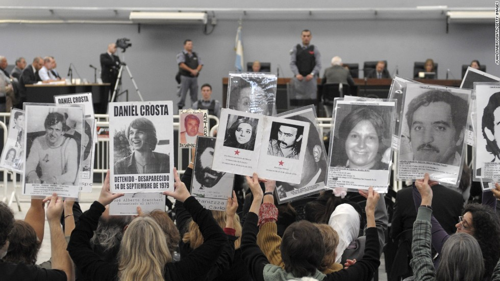 People hold portraits of missing relatives at the trial of former Argentina ruler Reynaldo Bignone in 2010. Charged with kidnap and torture, Bignone was sentenced to 25 years in prison -- and the 86-year-old has been convicted of other crimes since.