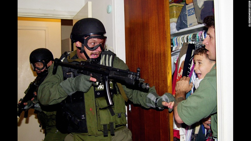 During a raid at a Miami home in 2000, armed federal agents confront Elian Gonzalez, 6, and one of the men who helped rescue the boy. Gonzalez watched his mother drown when the boat smuggling them from Cuba capsized. Under international law, U.S. authorities were required to return the boy to his father in Cuba.