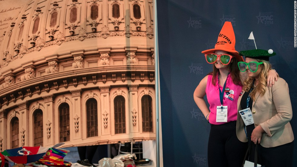 Two women pose is a photo booth with a picture of the U.S. Capitol in the background at CPAC on Thursday.