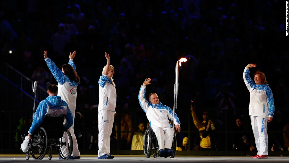 Paralympic torch bearers wave to the crowd.