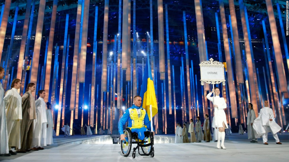Biathlete Mykhaylo Tkachenko carries the Ukrainian flag into the stadium.