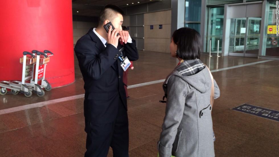 Una mujer habla a un miembro del personal en el aeropuerto de Beijing para obtener más información sobre el vuelo desaparecido.
