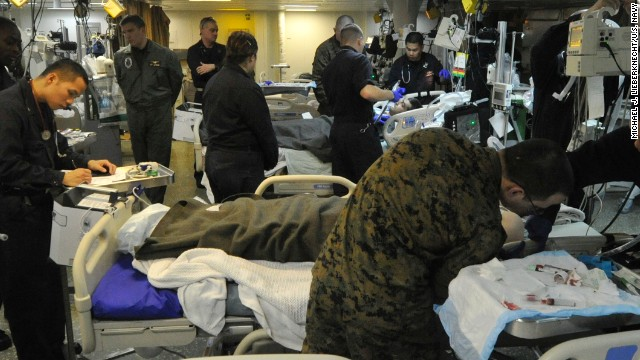 Medical personnel aboard the USS Bataan examine Turkish mariners rescued by a search and rescue swimmer.