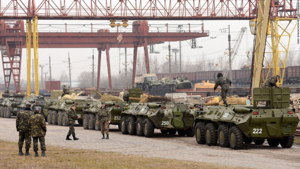 Ukrainian soldiers load armored personnel carriers into boxcars in the western Ukrainian city of Lviv on March 8.