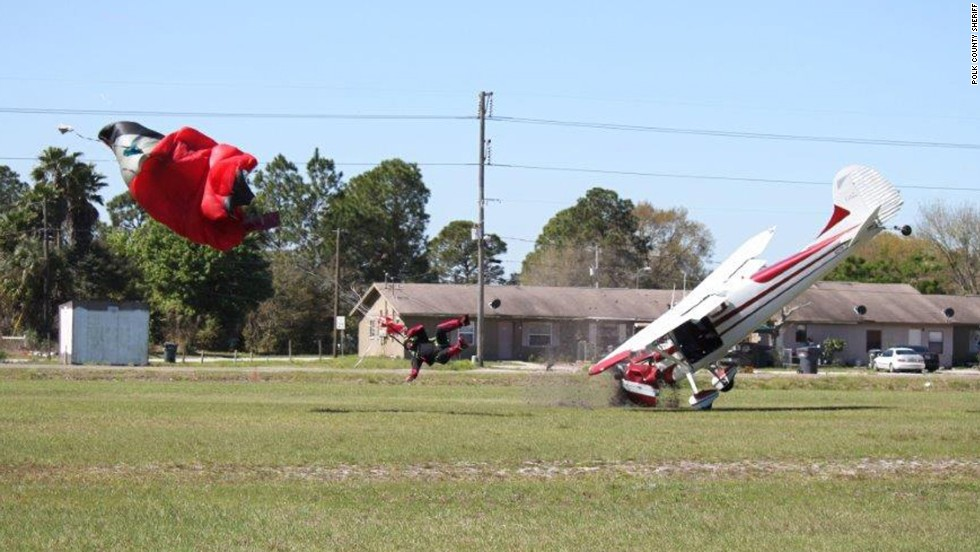The plane crashes nose first into the ground after hitting the parachute.