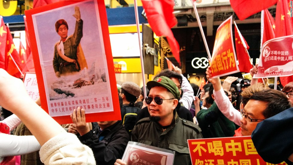 "A protester in a Communist costume holds a sign reading ""If you don't drink Chinese milk, are you still Chinese?"" To the left, an image of Hong Kong's embattled chief executive C.Y. Leung photoshopped onto Mao Zedong's body."
