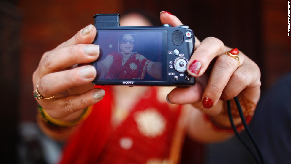 "MARCH 10 - KATHMANDU, NEPAL: A Nepalese woman takes a selfie outside a temple. People around the world marked International Women's Day on Saturday, celebrating women's achievements and campaigning for gender equality. Joining them was <a href=""http://edition.cnn.com/2014/03/08/living/cnnwomen-tweetchat-as-it-happened/index.html"">CNN's Leading Women team which hosted a global discussion on equality</a>."