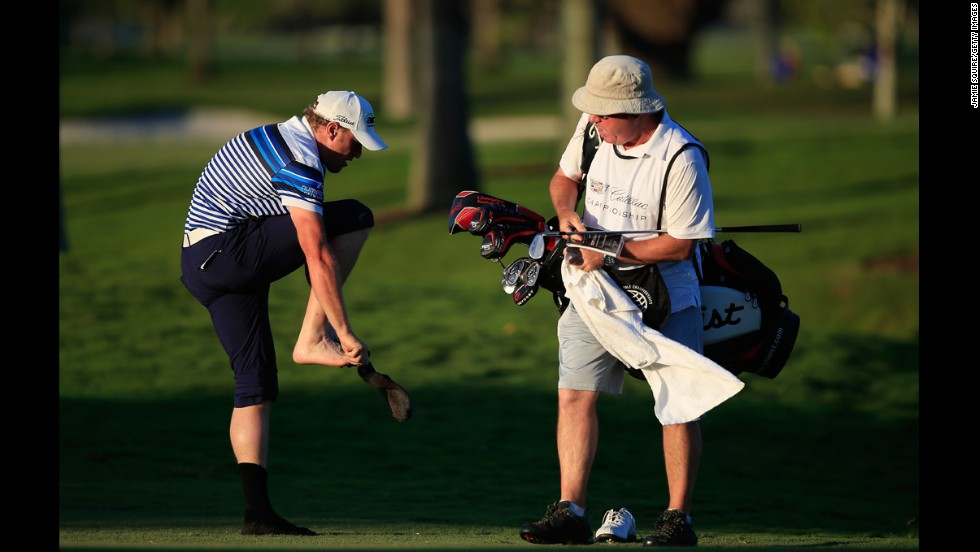 Pro golfer Jamie Donaldson removes his socks as he prepares to hit a shot from the water's edge Friday, March 7, during the second round of the WGC-Cadillac Championship in Doral, Florida.