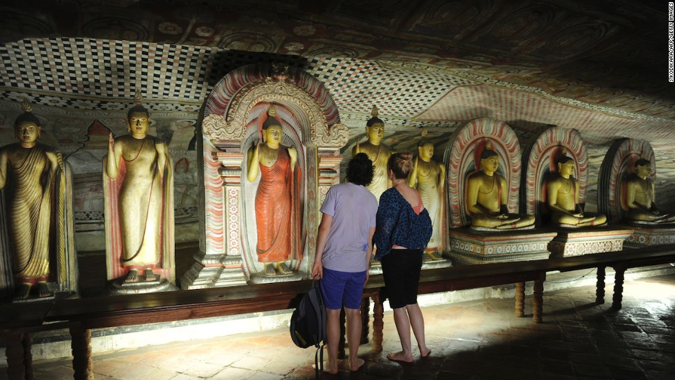 Buddhist statues line the walls in Dambulla's cave temple, a UNESCO World Heritage Site that dates to the 1st century BC.