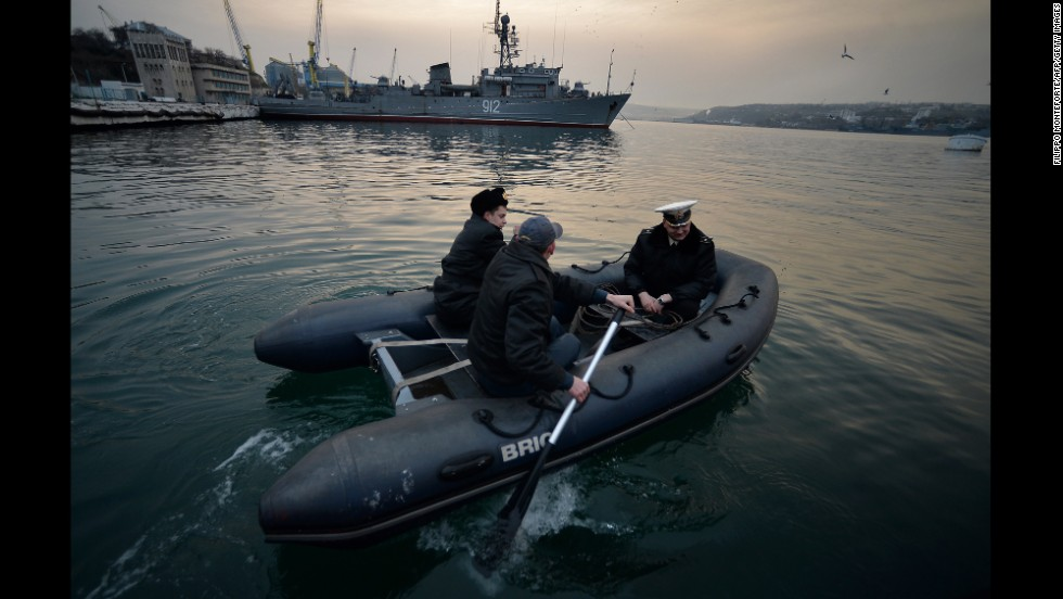 Ukrainian naval officers board a boat in front of the Russian minesweeper Turbinist in Sevastopol's harbor on March 11.