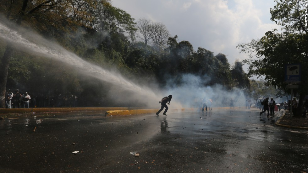 Protesters run from a water cannon blast shot by police in Caracas on March 12.