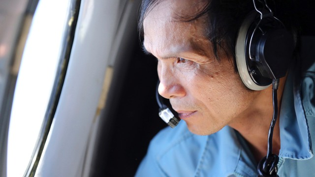 Vietnamese Air Force Col. Pham Minh Tuan watches out from a window on board a flying aircraft during a mission to search for the missing Malaysia Airlines flight MH370 in the Gulf of Thailand over the location where Chinese satellite images showed possible debris from the missing Malaysian jetliner, Thursday, March 13, 2014.