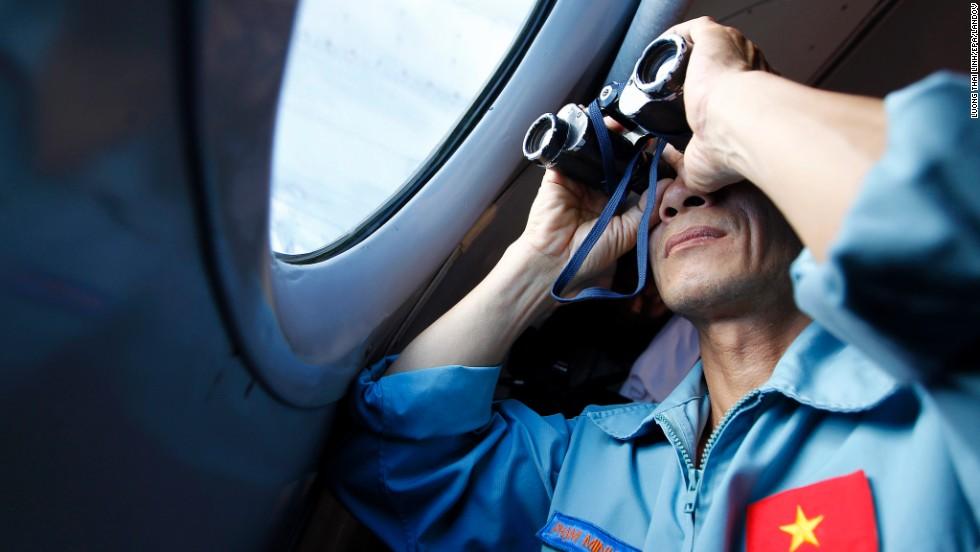 Un funcionario militar de Vietnam mira por un binocular en busca del avión de malaysia Airlines que desapareció el 8 de marzo.