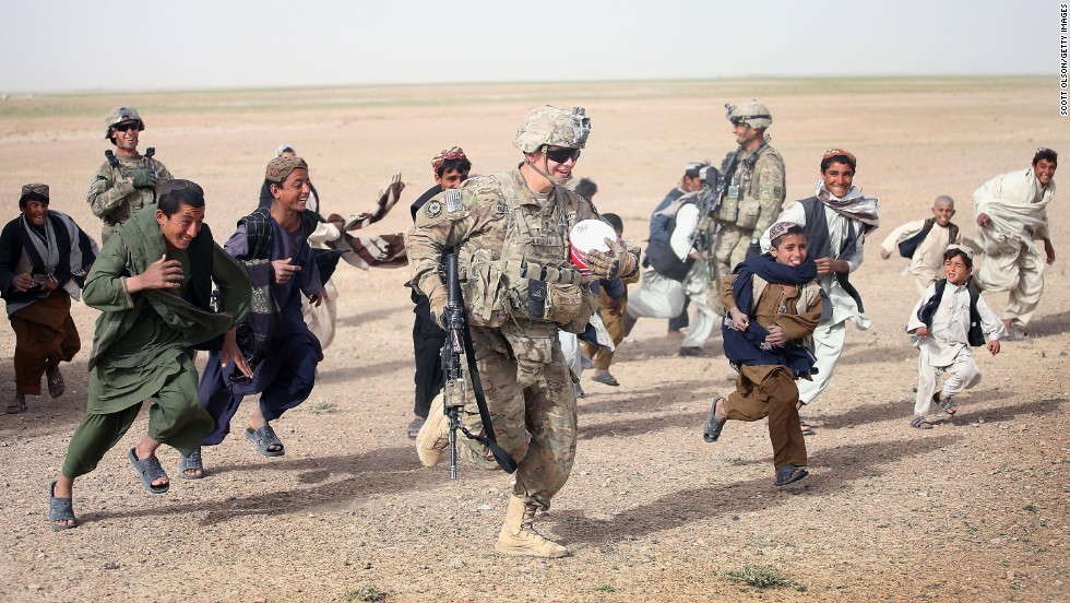 U.S. Army Spc. Taylor Burcham runs with a soccer ball that he gave to children near Kandahar, Afghanistan, on Sunday, March 9.