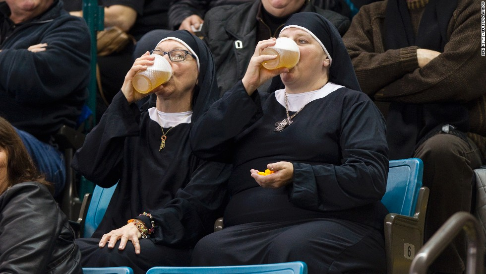 Two women wearing nun outfits drink beer while they watch curling Saturday, March 8, in Kamloops, British Columbia.