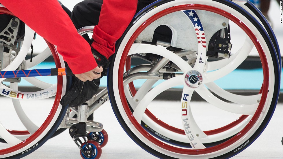 Joseph Jimmy, right, steadies the chair of Lino Meghan of the United States during a curling match against South Korea on March 8.