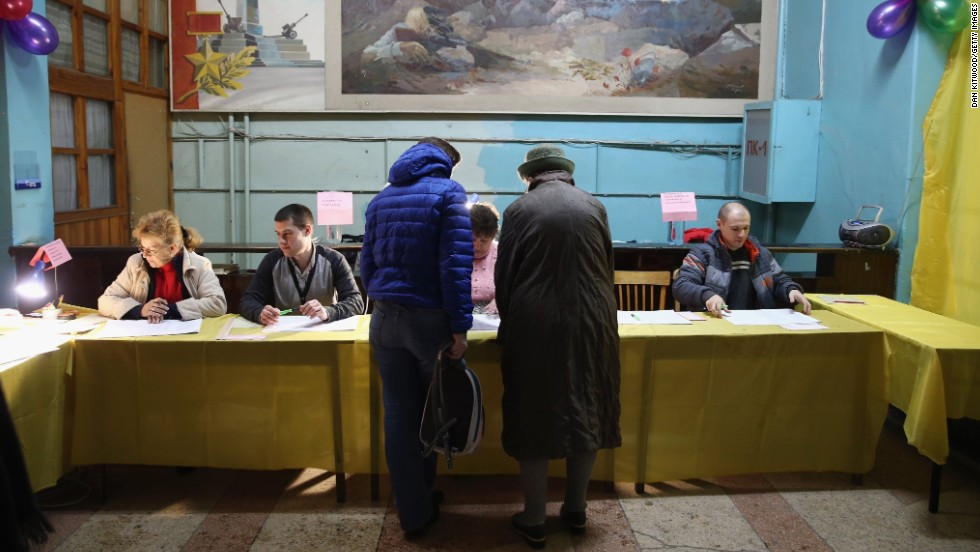 Voters talk to election officials inside a polling station in Simferopol.