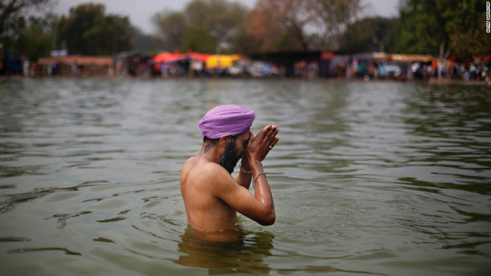 A man prays as he washes himself before a religious procession in Punjab, India, on March 17.