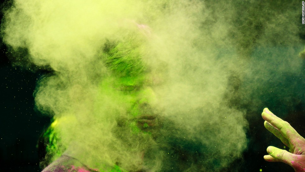 A man throws colored powder on another man March 17 in Mumbai.