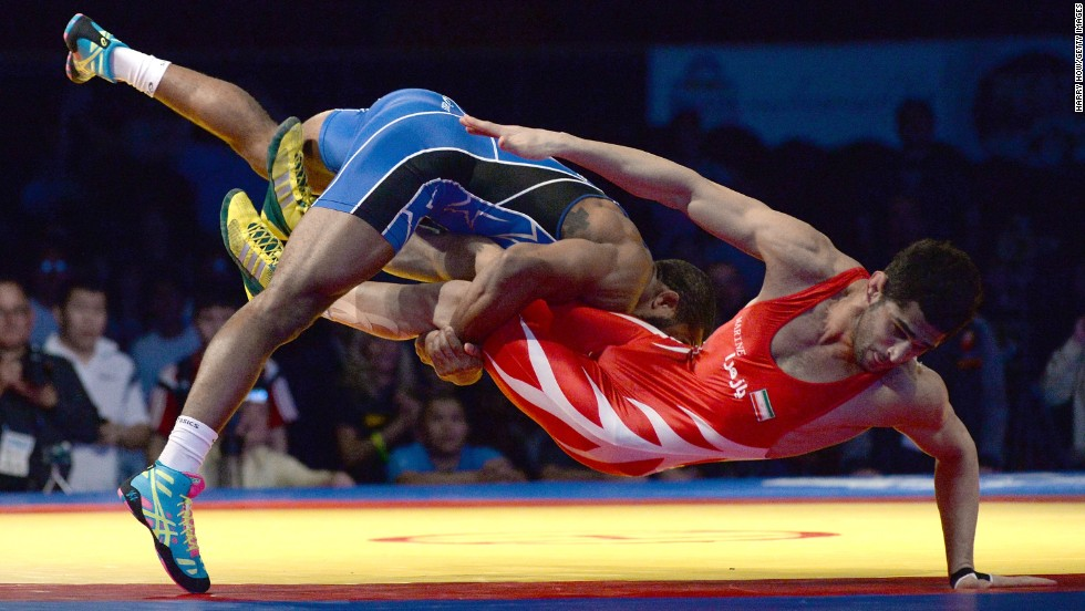 Jordan Burroughs of the United States, left, takes down Ezzatollah Akbari Zarinkolaei of Iran during the FILA Wrestling World Cup in Inglewood, California, on Saturday, March 15.