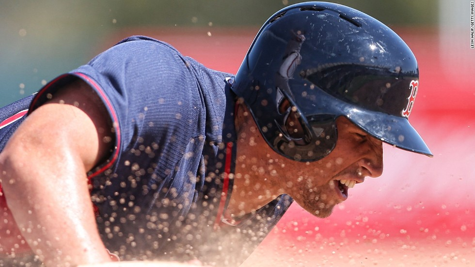 Garin Cecchini of the Boston Red Sox slides into first base during a spring training game against Baltimore on Tuesday, March 11, in Sarasota, Florida.