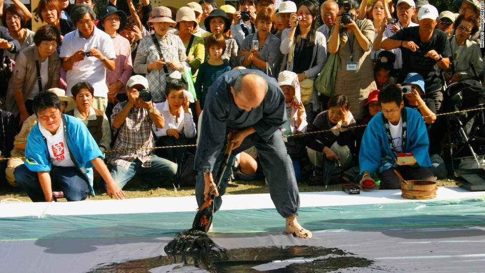 "Calligraphy masters pace barefoot around a ""canvas"" (a large vinyl sheet spread on the ground) in a balletic whirl, wielding a heavy brush longer than their arm."