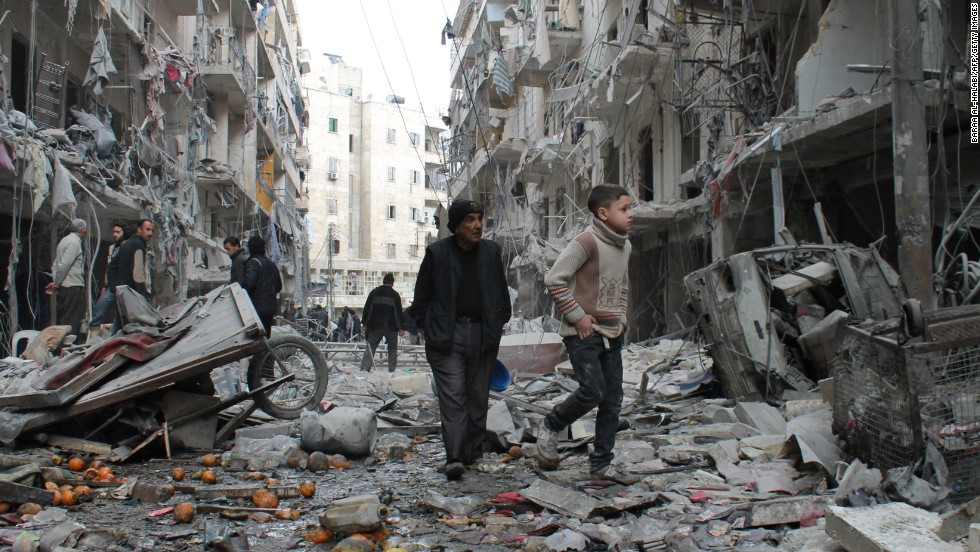 An elderly man and a child walk among debris in a residential block of Aleppo on March 18.