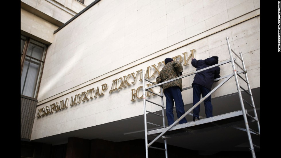 Nameplates on the front of the Crimean parliament building get removed Tuesday, March 18, in Simferopol.