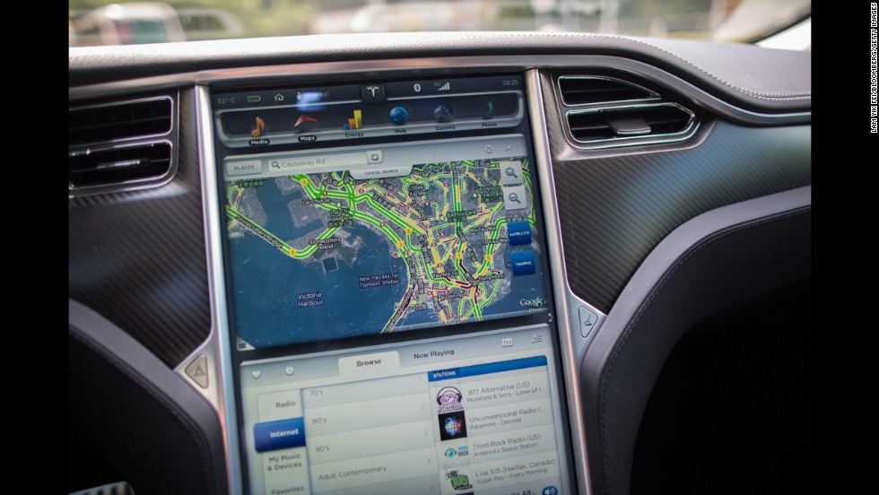 A Google map is displayed on a screen in a Tesla Model S sedan.