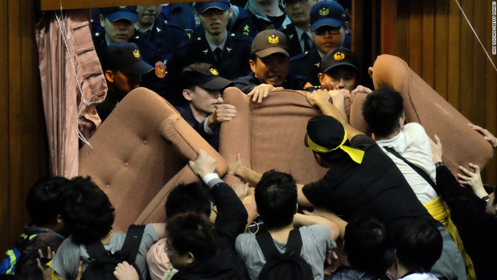Police officers try to enter the Legislature while it is blocked and occupied by activists on March 19.