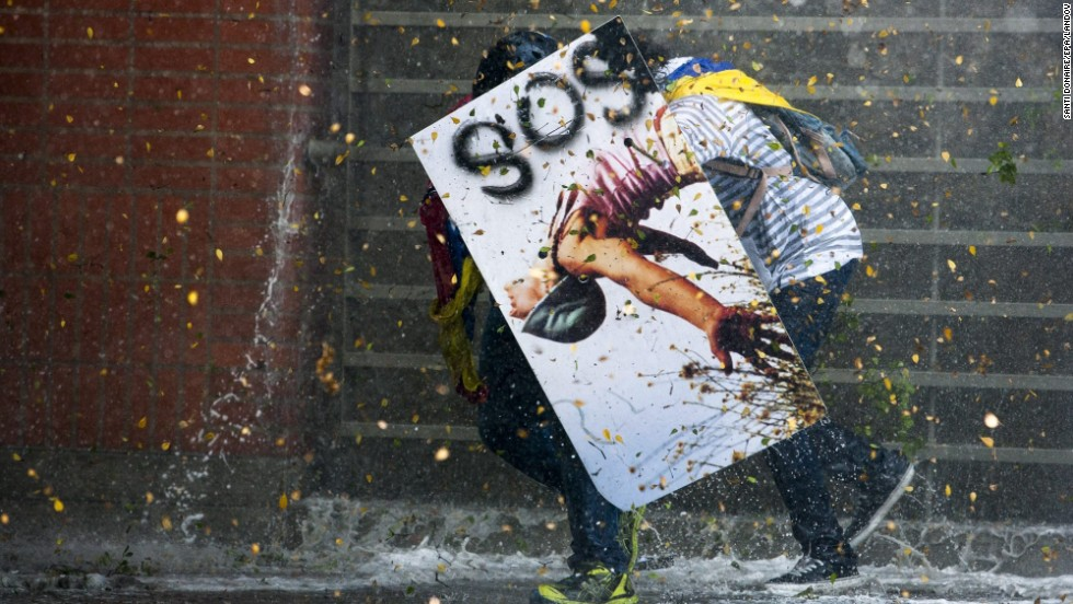 "Demonstrators clash with members of the Bolivarian National Police after a mass meeting called by opposition students in Caracas, Venezuela, on Thursday, March 20. For weeks, demonstrators, unhappy with Venezuela's economy and rising crime, have been <a href=""http://www.cnn.com/2014/02/18/world/gallery/venezuela-protests/index.html"">clashing with security forces</a>."