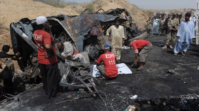 Investigators sift through the wreckage of a deadly bus and tanker crash in Pakistan's Baluchistan province on March 22, 2014.